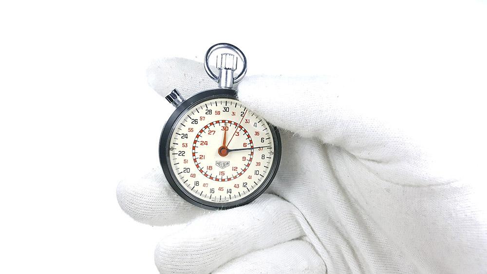 Chronomètre HEUER-LEONIDAS ref. 513.202 (cadran damier) --- plan rapproché avec main --- ikonicstopwatch.com