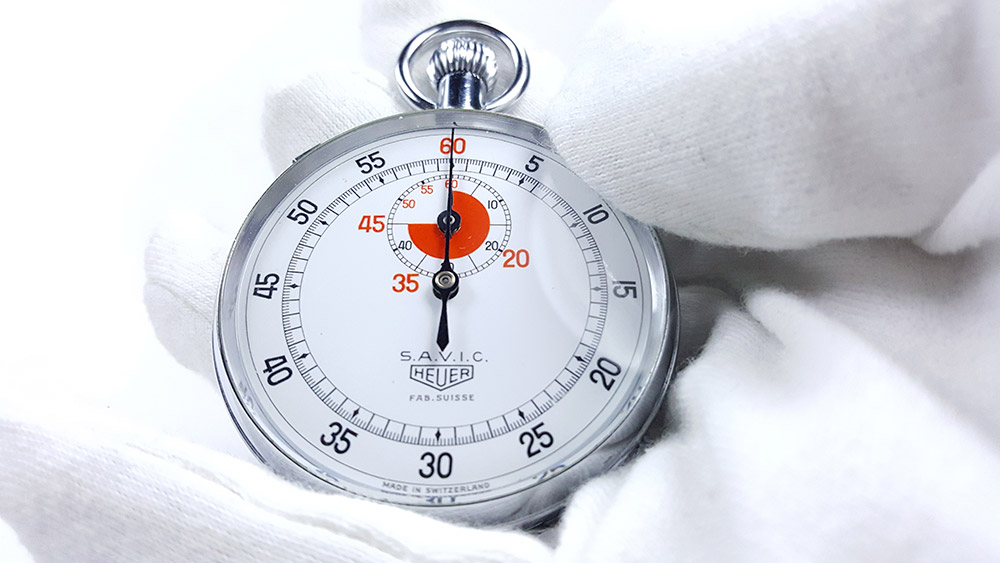 Chronomètre vintage HEUER ref. 907 (version S.A.V.I.C) --- plan rapproché avec main --- ikonicstopwatch.com