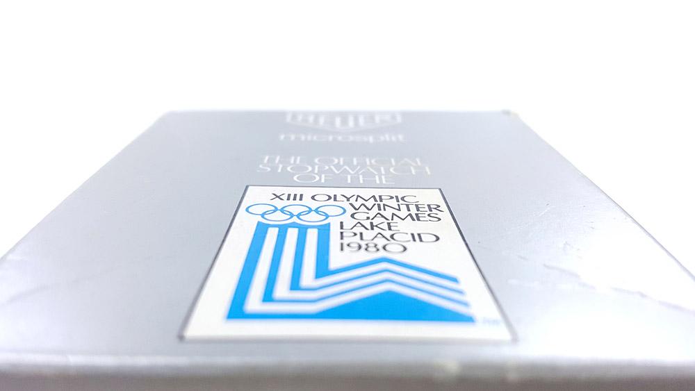 Chronomètre vintage HEUER ref. 230 microsplit (version jeux olympiques lake placid) --- gros plan logo jeux olympiques --- ikonicstopwatch.com