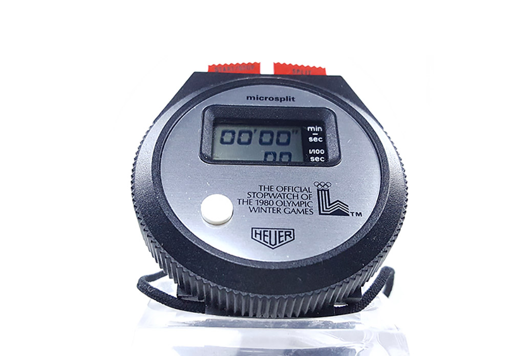 Vintage HEUER stopwatch ref. 230 microsplit (lake placid olympic games version) --- close side view (cover) --- ikonicstopwatch.com