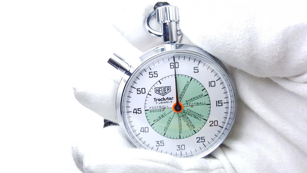 Chronomètre vintage HEUER ref. 653.302 trackstar (allsports) --- plan rapproché avec main --- ikonicstopwatch.com